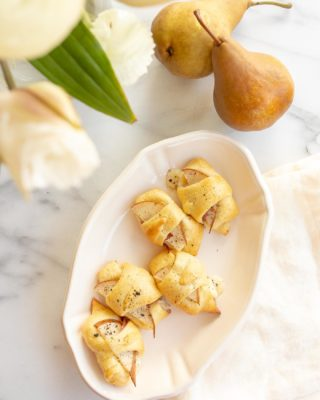 baked cheese pear and proscuitto crescent roll appetizer in a dish with flowers and pears