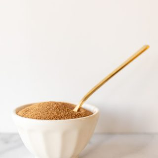 White marble surface, white ceramic bowl of cinnamon sugar recipe with gold spoon sticking up.