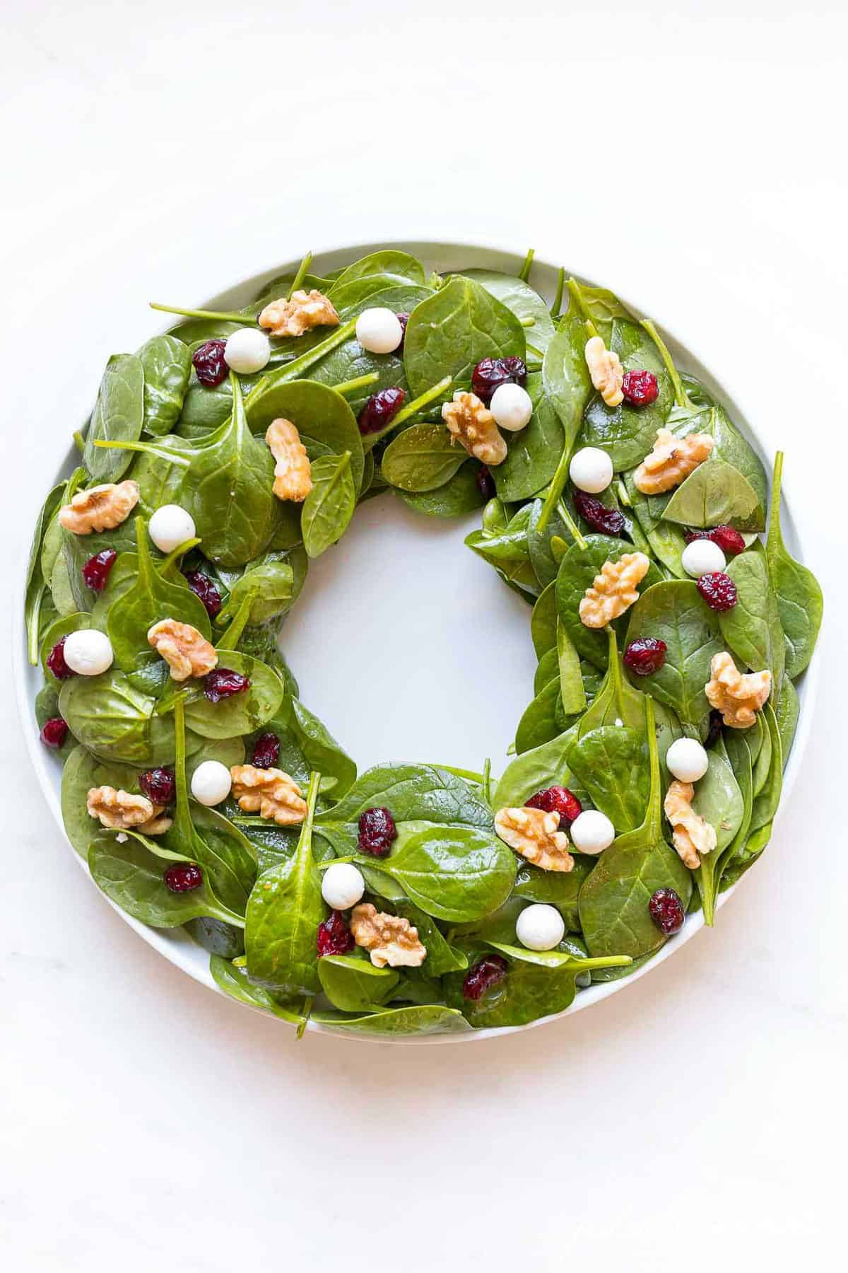 christmas salad in shape of a wreath with goat cheese cranberries and nuts to look like berries