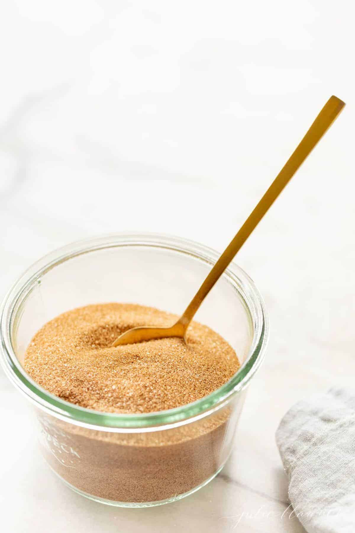 White marble surface, clear glass jar of cinnamon sugar recipe with gold spoon sticking up.