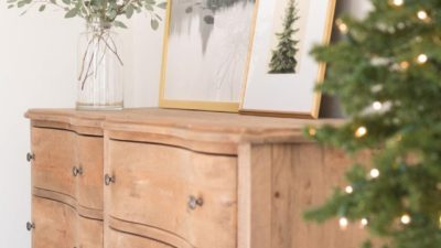 A soft wood dresser in a bedroom with simple Christmas decor.