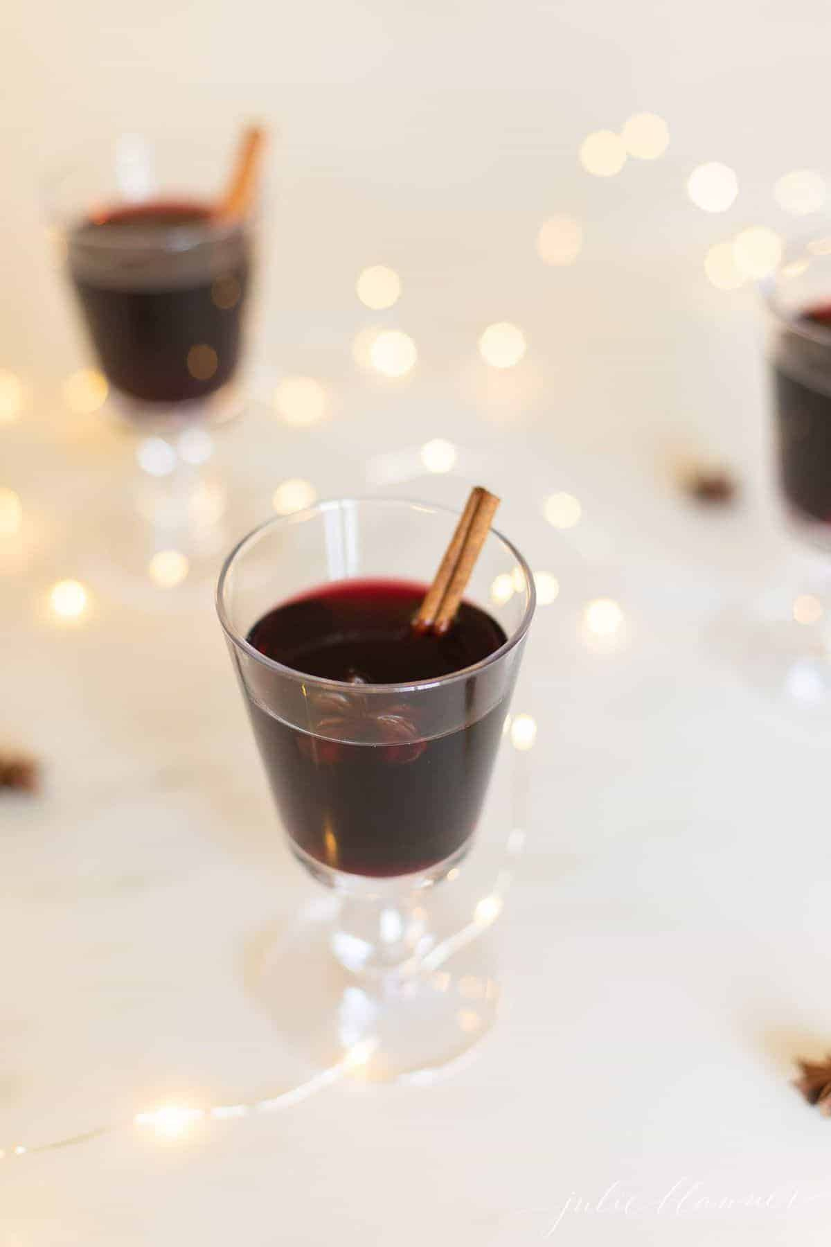 Glasses full of a gluhwein recipe, sparkling lights scattered around.