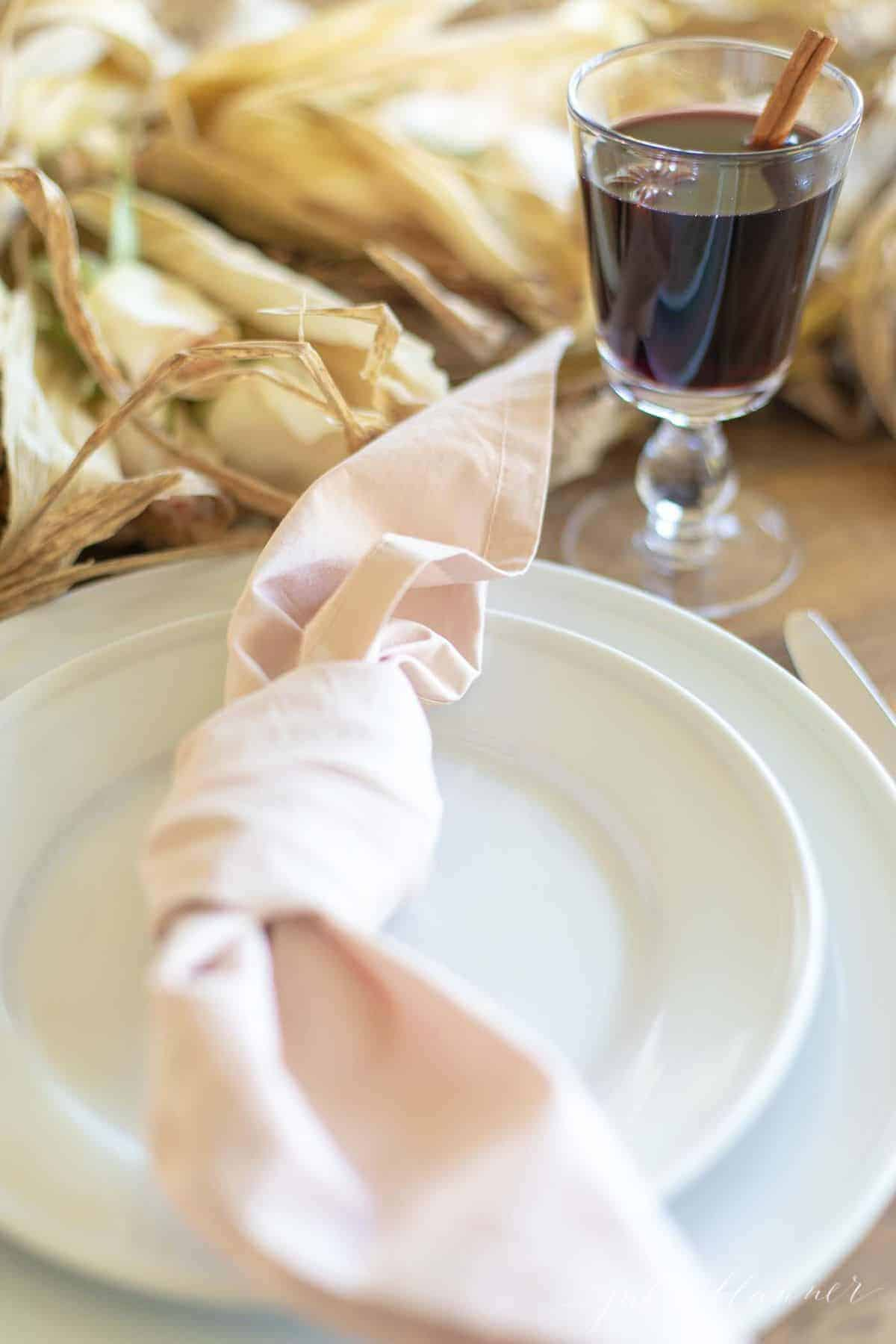 White plates on a fall table, pink napkin tied on plate, mulled wine in the background.