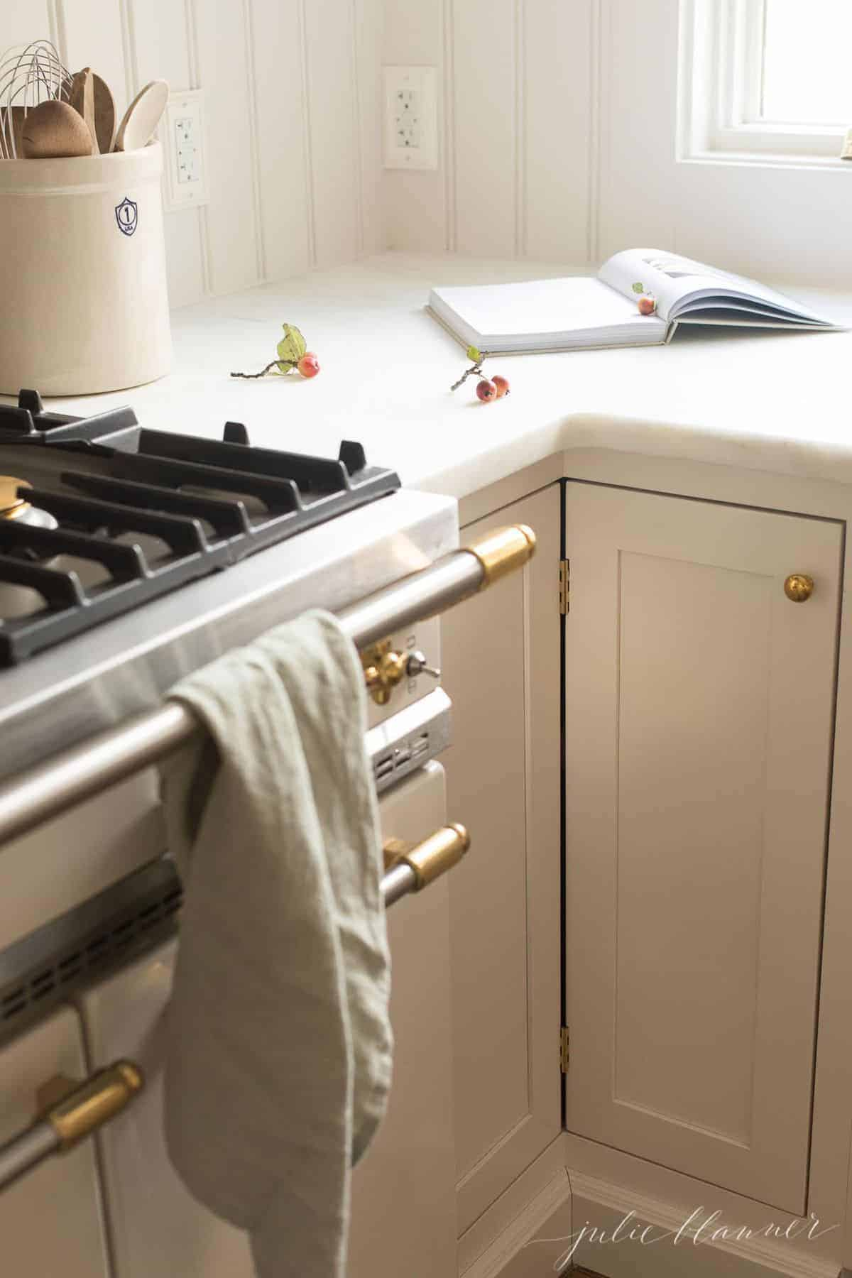 French range with white cabinets, open cookbook.
