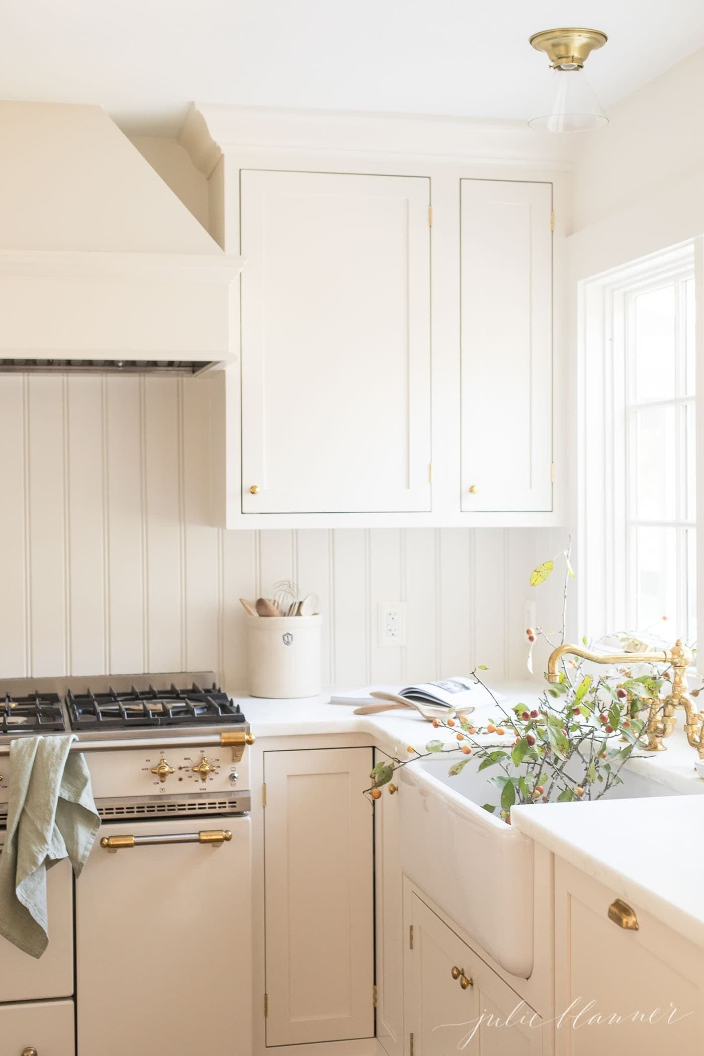White kitchen cabinets with fall branches in the farm sink.