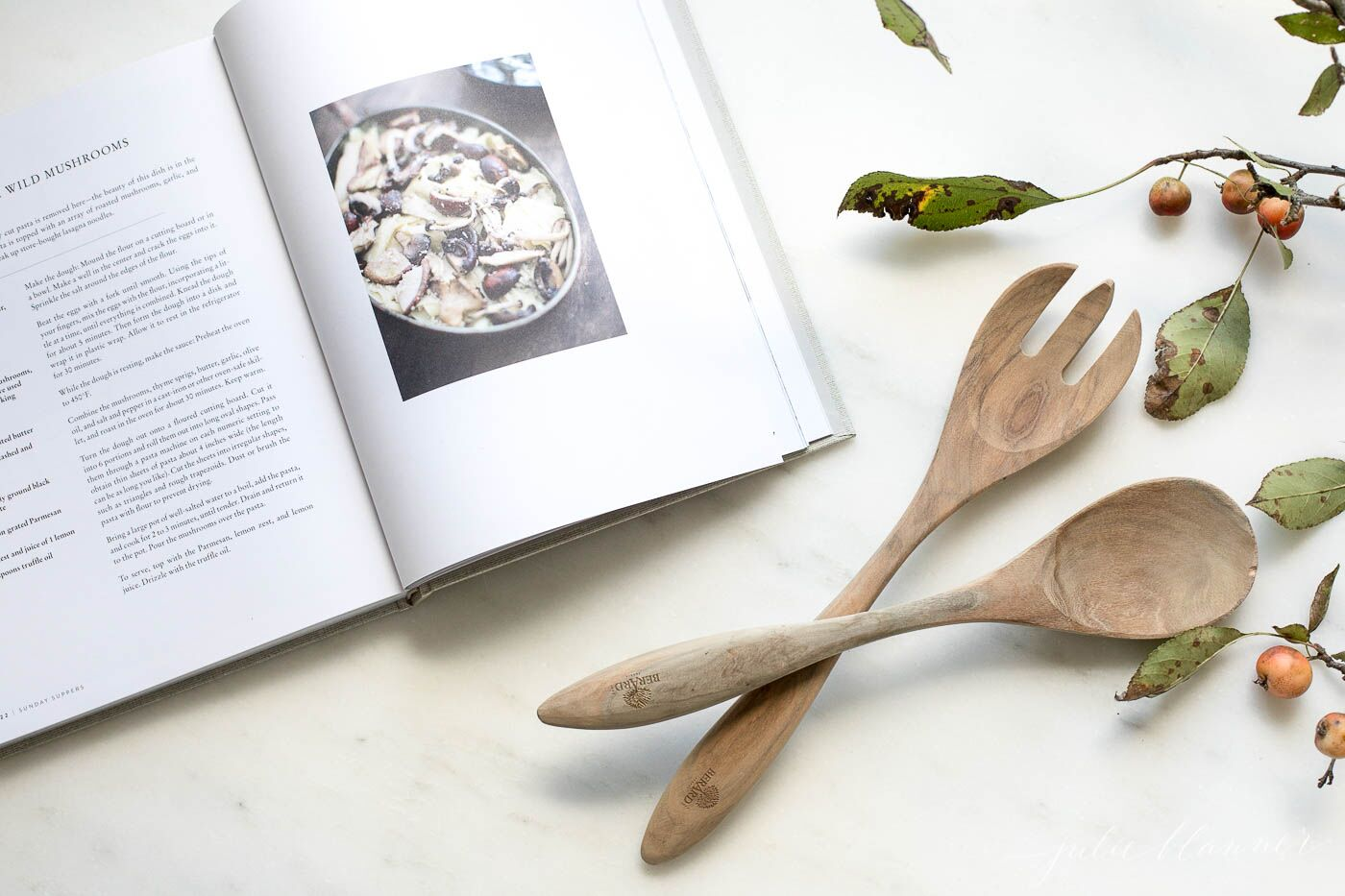 Marble surface, open cookbook, fall berries and wooden spoons to the side.