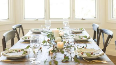 Farm table set for Thanksgiving dinner, candles and branches down the center.