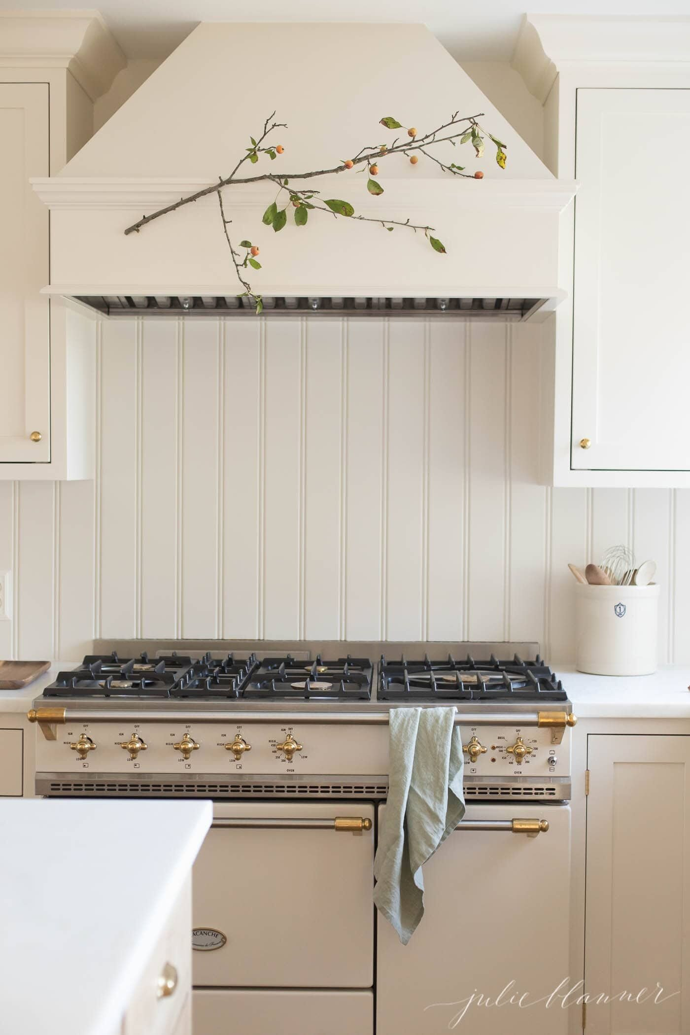 White kitchen cabinets with a fall branch on the range hood.