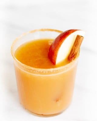 Cinnamon liquor cocktail glass on marble surface, garnished with apple slice and cinnamon sticks.