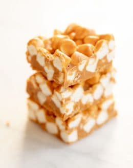 Stack of three homemade no bake butterscotch candy bars on a marble surface.