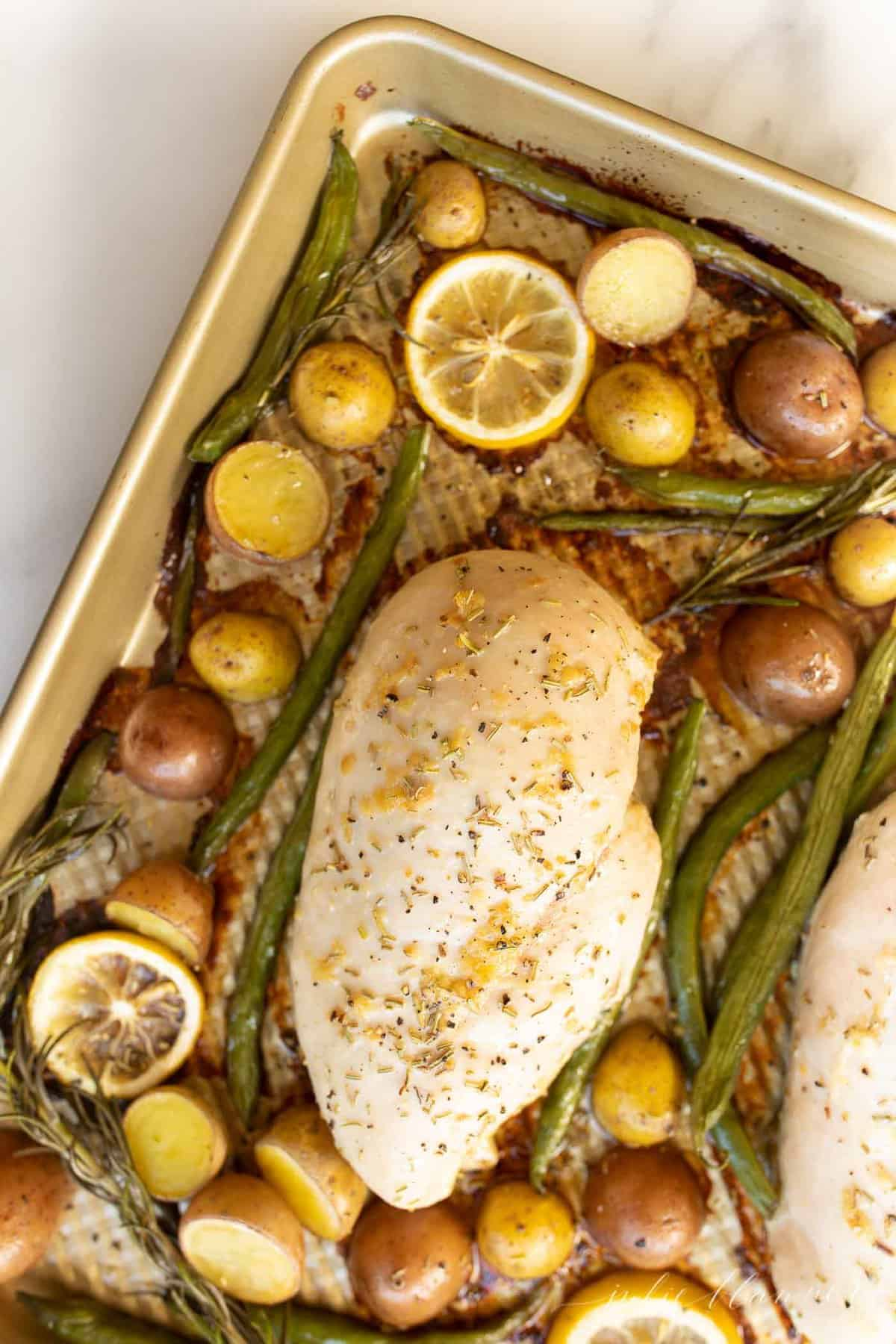 Gold baking sheet with a baked chicken breast, lemon slices and roasted veggies.
