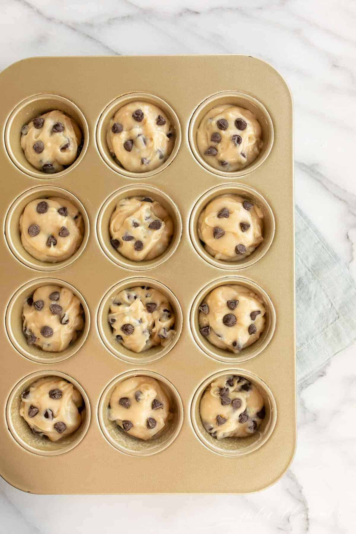 chocolate chip cookie muffin batter in muffin tin