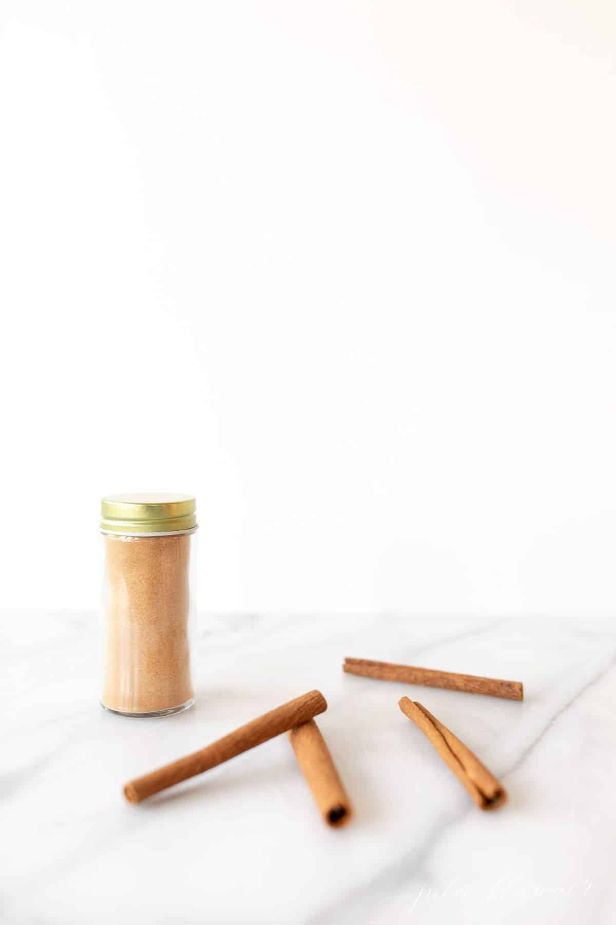 Marble surface with a glass spice jar of cinnamon sugar, cinnamon sticks strewn about.