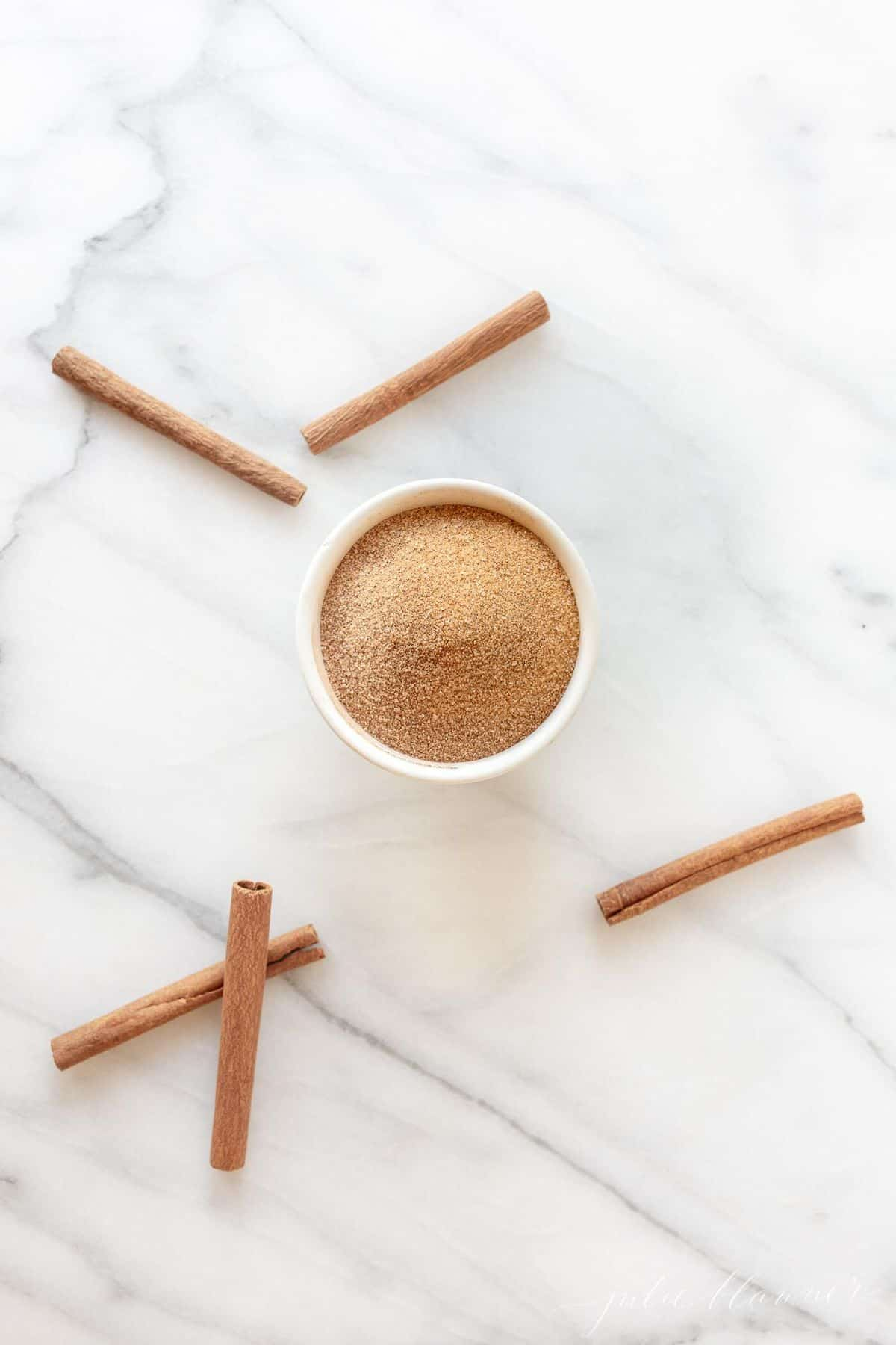 Marble surface with a bowl of the perfect cinnamon sugar ratio, cinnamon sticks strewn about.