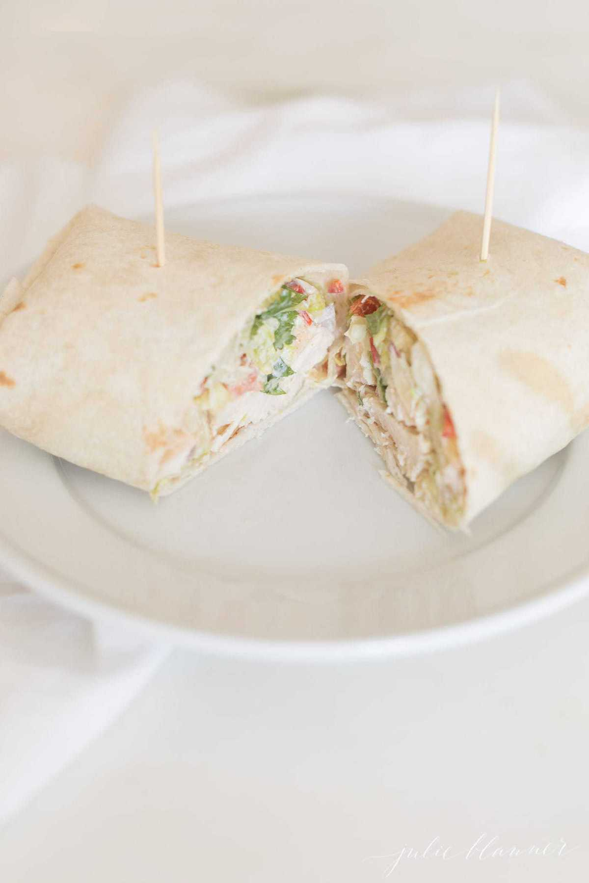 White plate with a chicken tortilla wrap split in two.