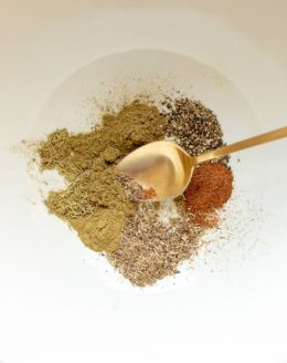 White bowl with poultry seasoning mix, gold spoon stirring.