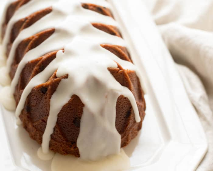 White tray with a pound cake loaf resting on top, glaze dripping onto surface.