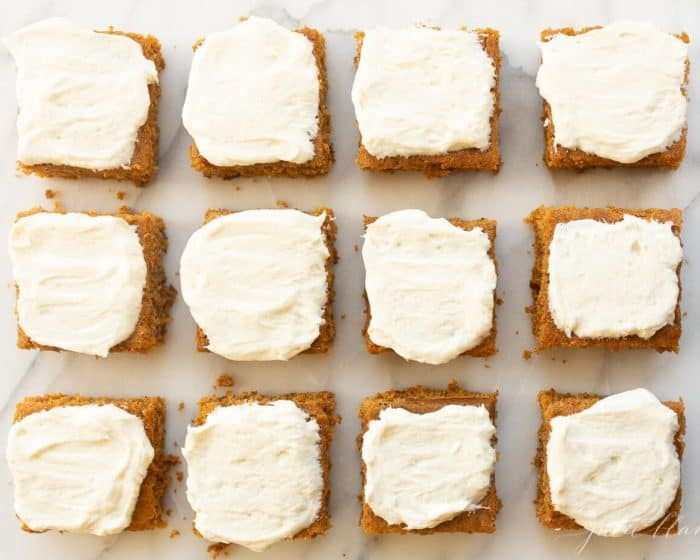 White surface with 12 cut pumpkin squares covered in frosting.