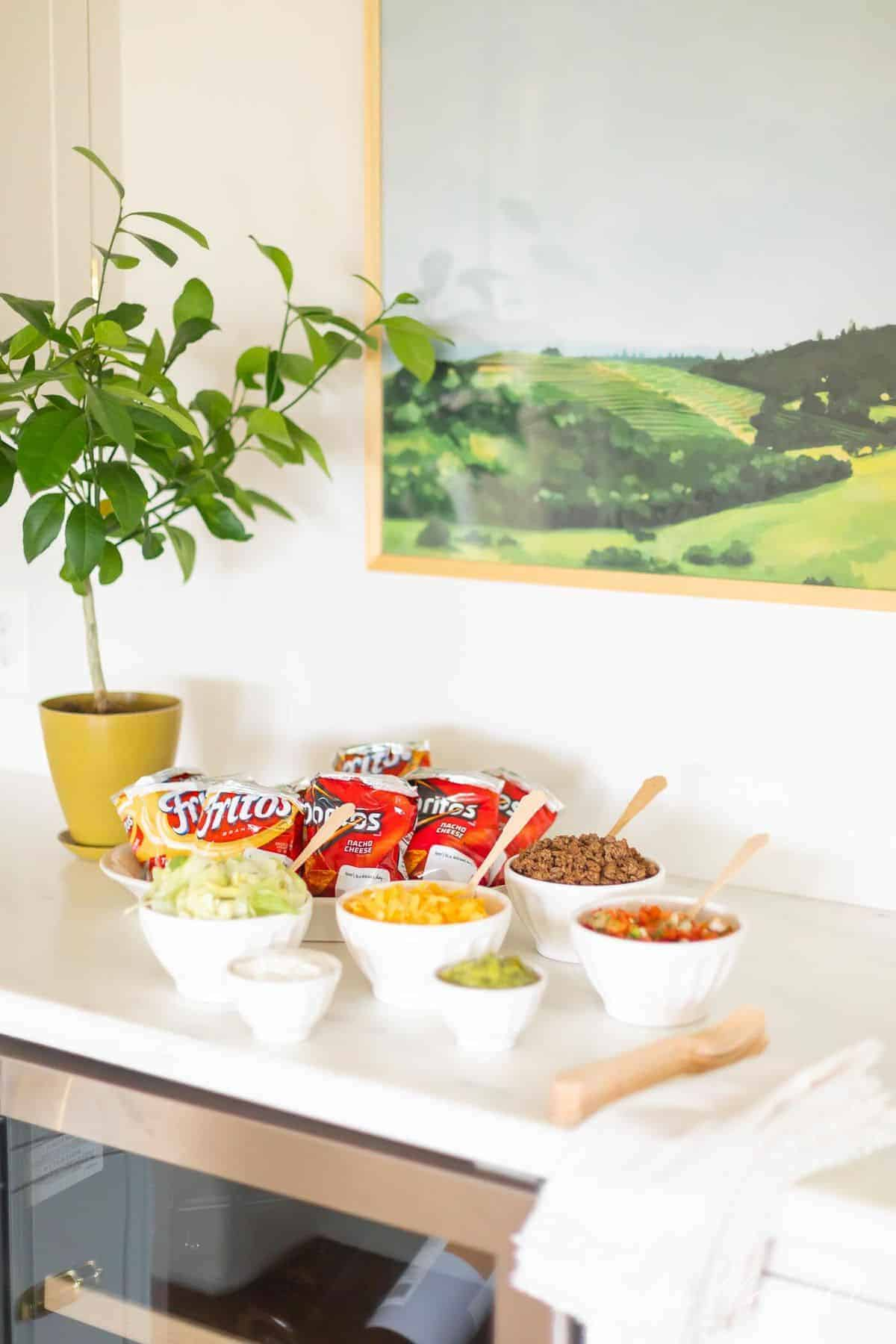 Kitchen walking taco bar display, with chip bags and white bowls of taco toppings.
