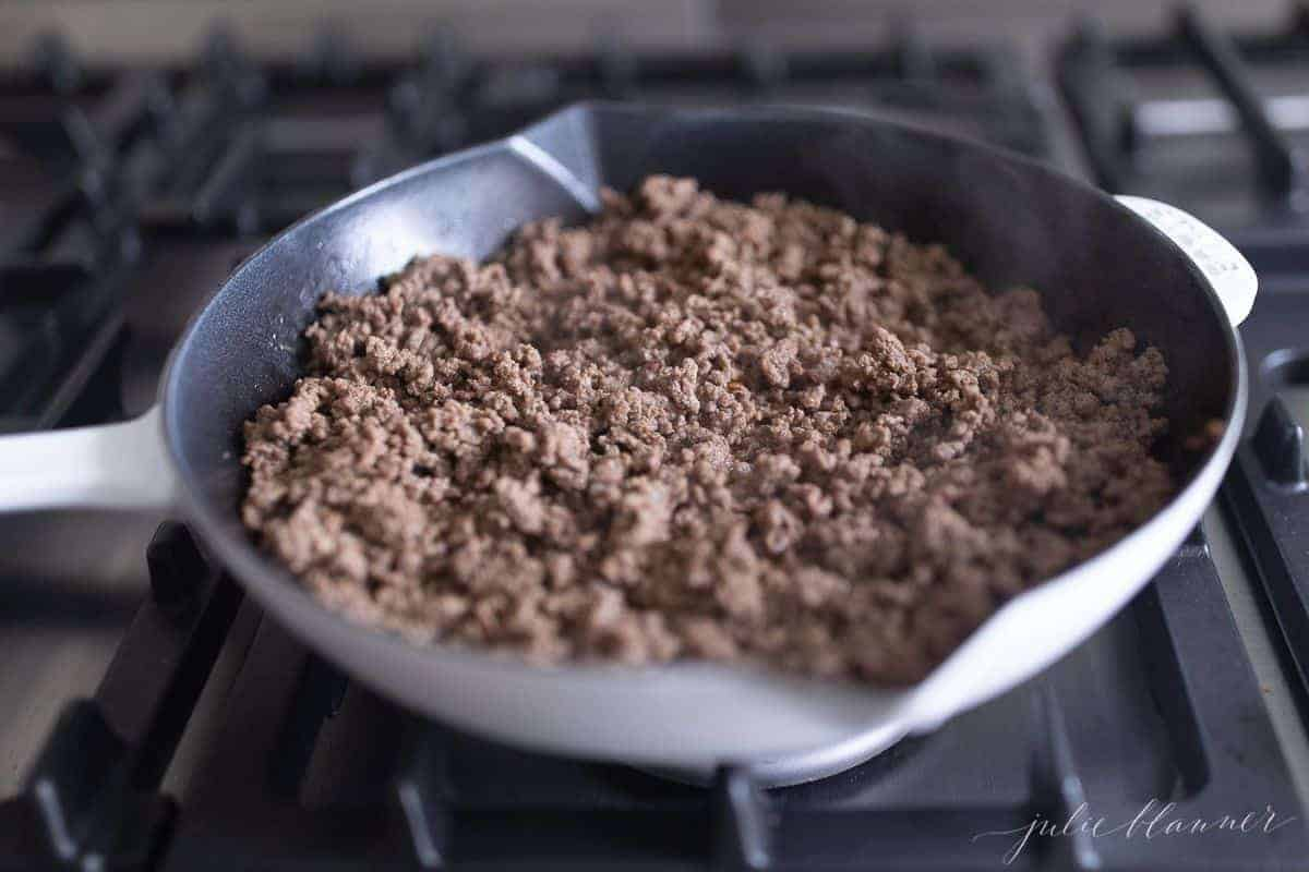 Stovetop, with a skillet with fully cooked ground beef.