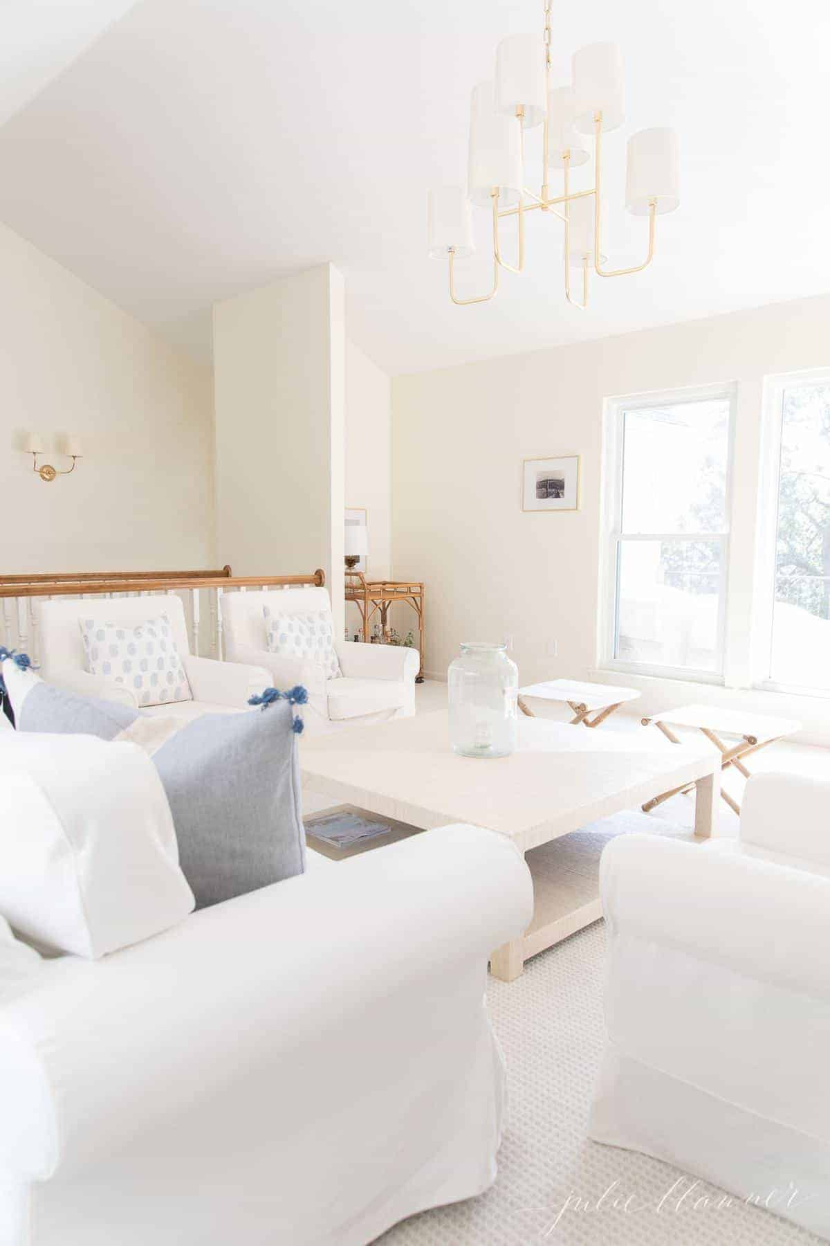 White living room with white sofas and large beige coffee table, brass chandelier above.