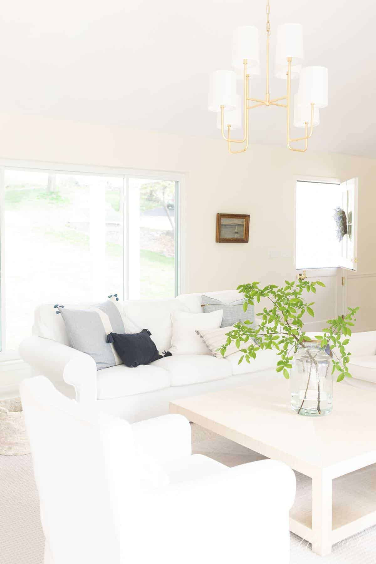 White living room with white Ikea couch covers and large beige coffee table, brass chandelier above.