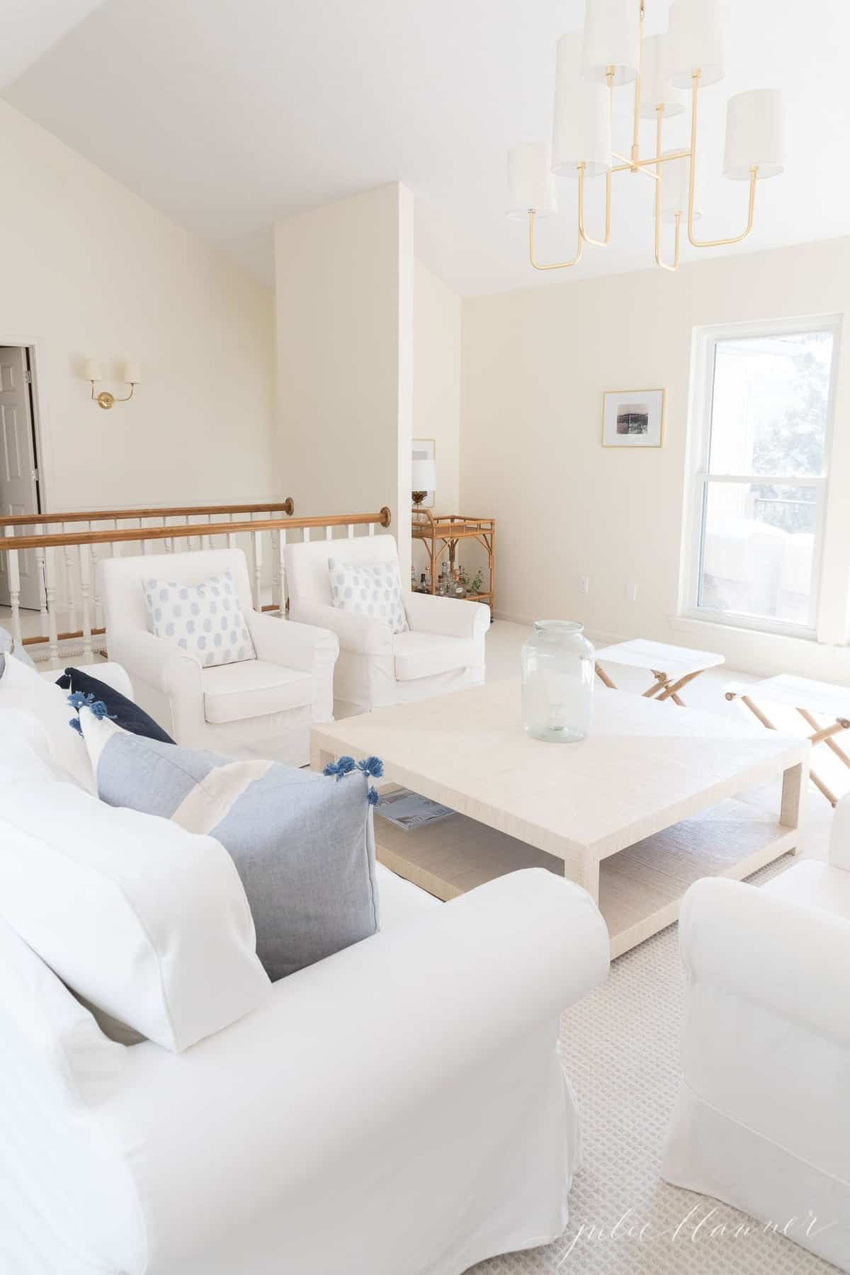 White living room with white Ikea Ektorp sofas and large beige coffee table, brass chandelier above.