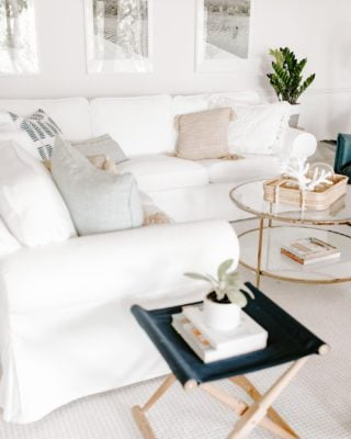 White living room with white sofa, glass coffee table and pair of navy blue chairs.