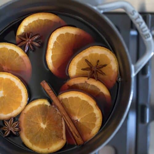 a gray cast iron pot on the stove with mulled wine, orange slices and cinnamon sticks.
