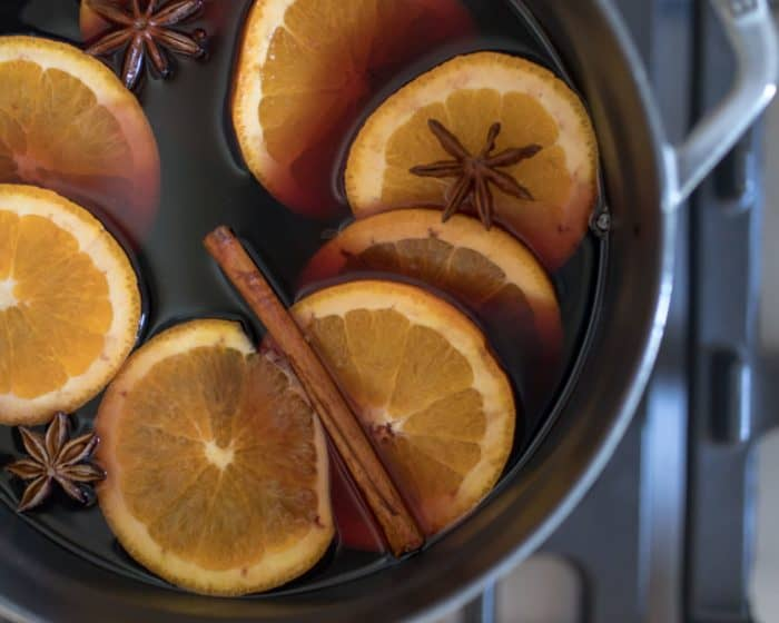 Gray enameled cast iron pot on stove top with mulled wine inside.