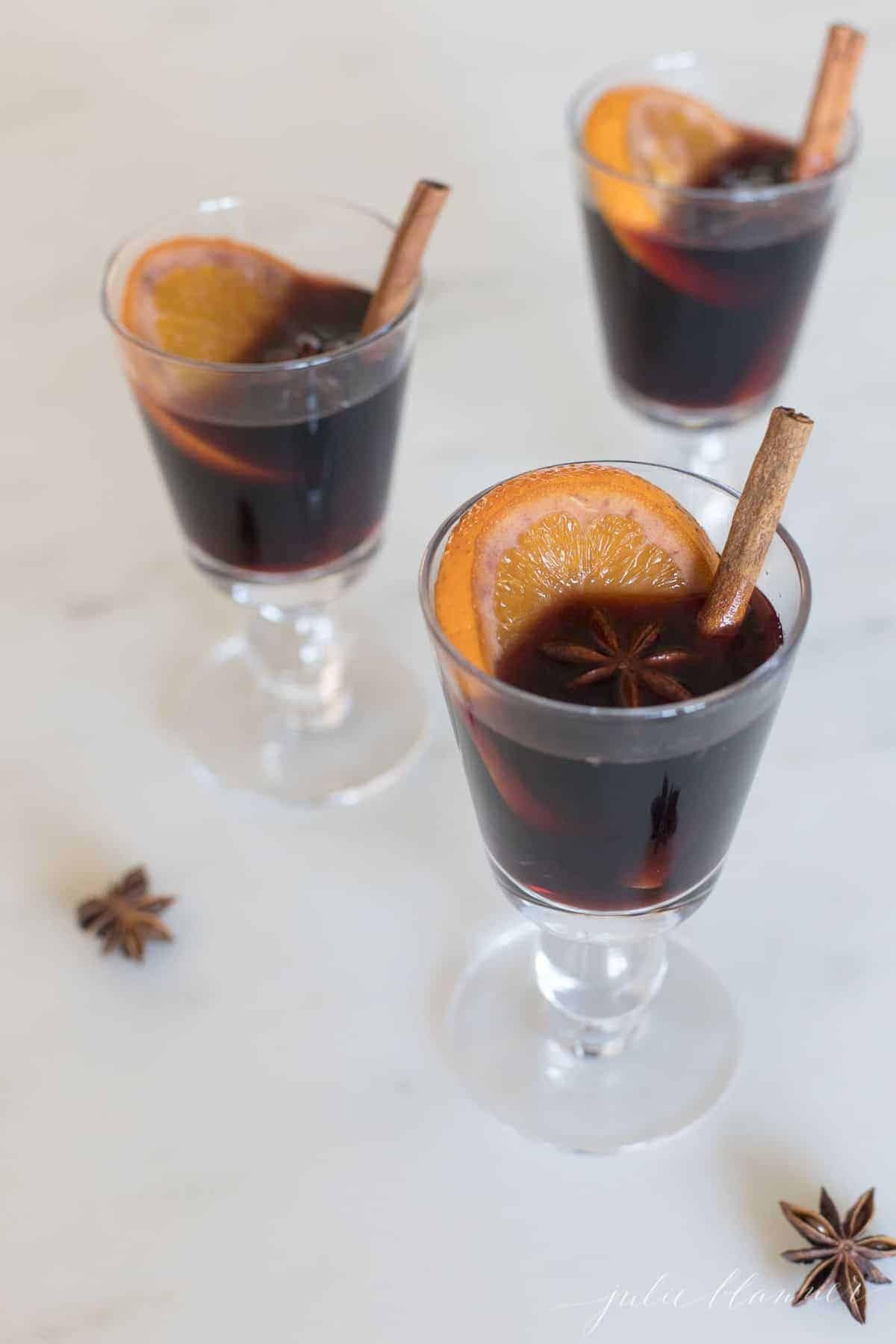 clear glasses full of mulled wine, cinnamon stick and orange slice to the side.