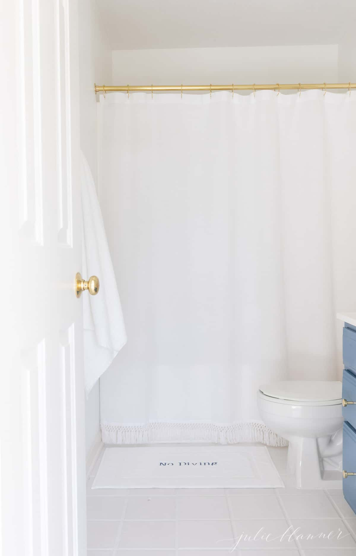 white bathroom with nautical blue nods and brass shower curtain rod