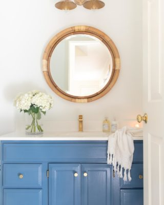 nautical bathroom with blue vanity brass faucet round rattan mirror flowers and hand towel