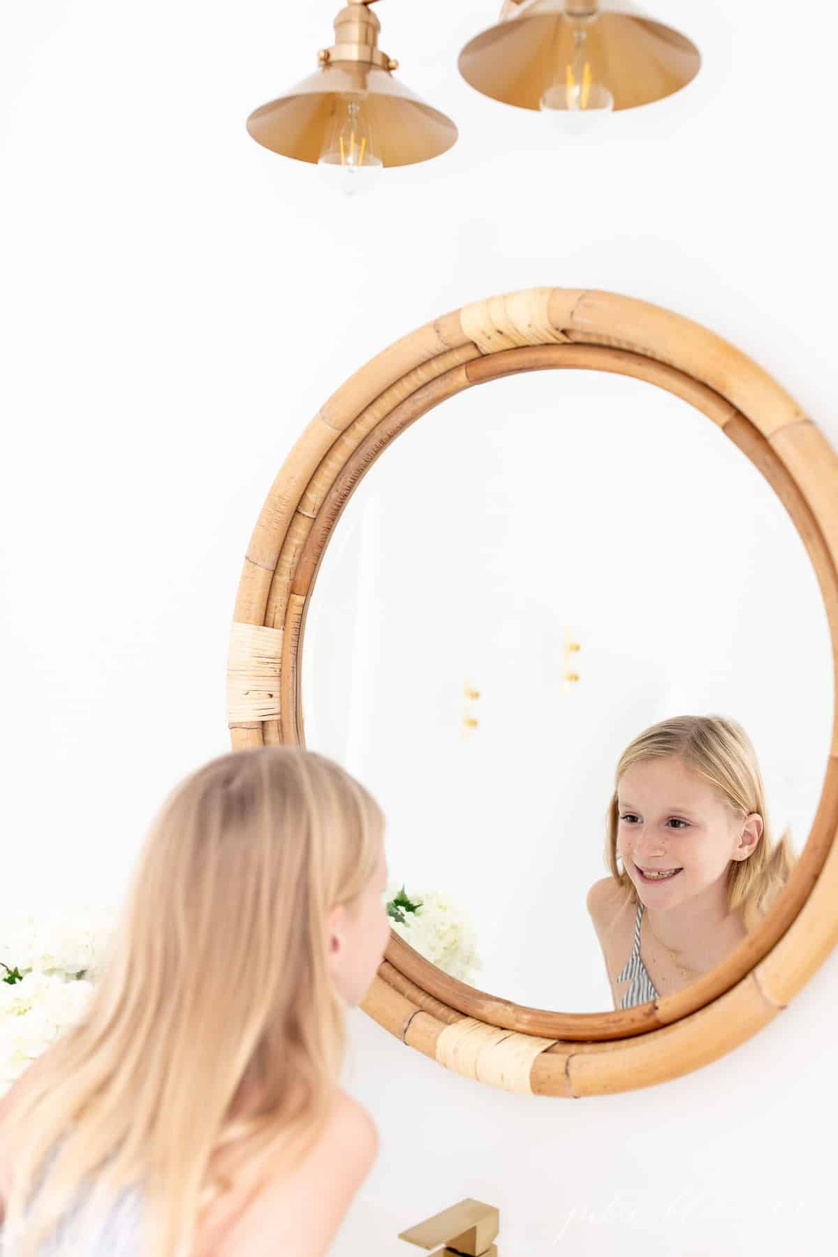 girl looking into round rattan mirror with nautical light overhead