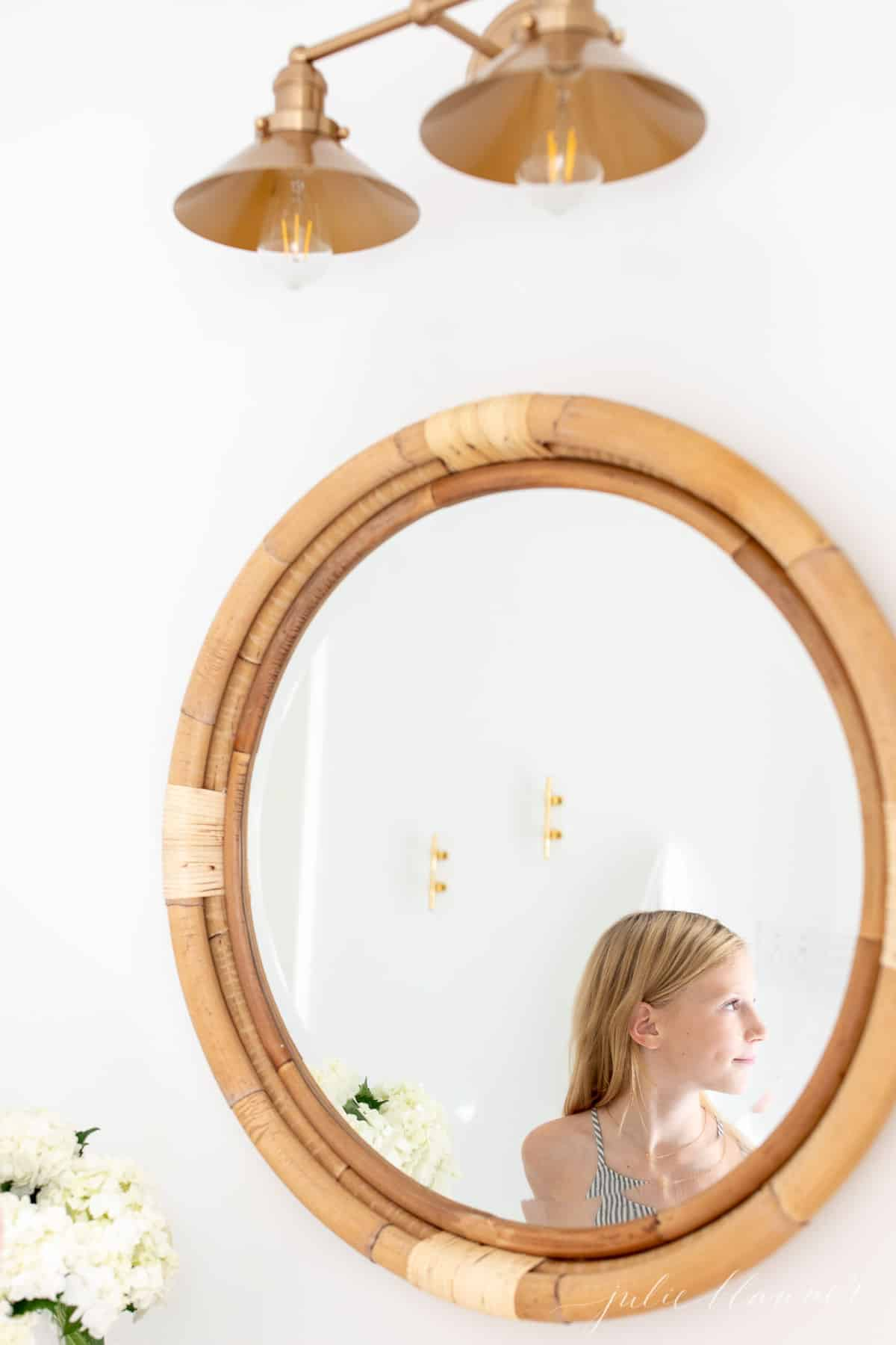 brass nautical light bathroom sconce with girl in mirror reflection