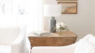 White Pottery Barn slipcovered sofas, antique wooden table with a blue lamp and simple decor in a living room.