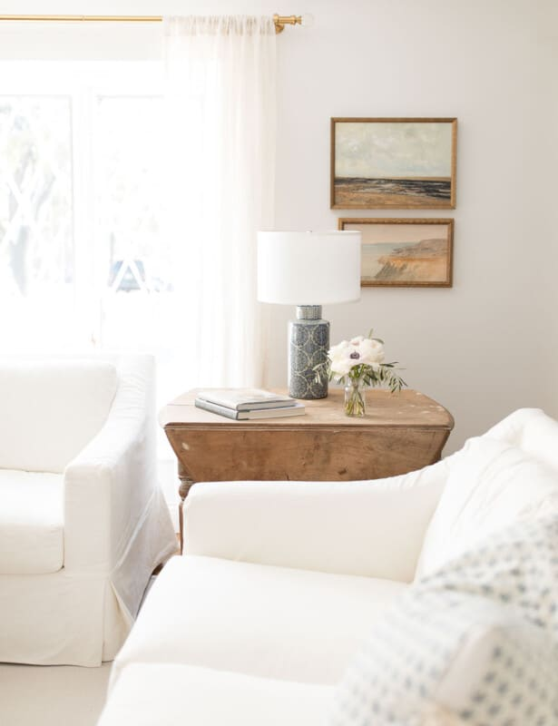 A living room with white sofas and a wooden side table