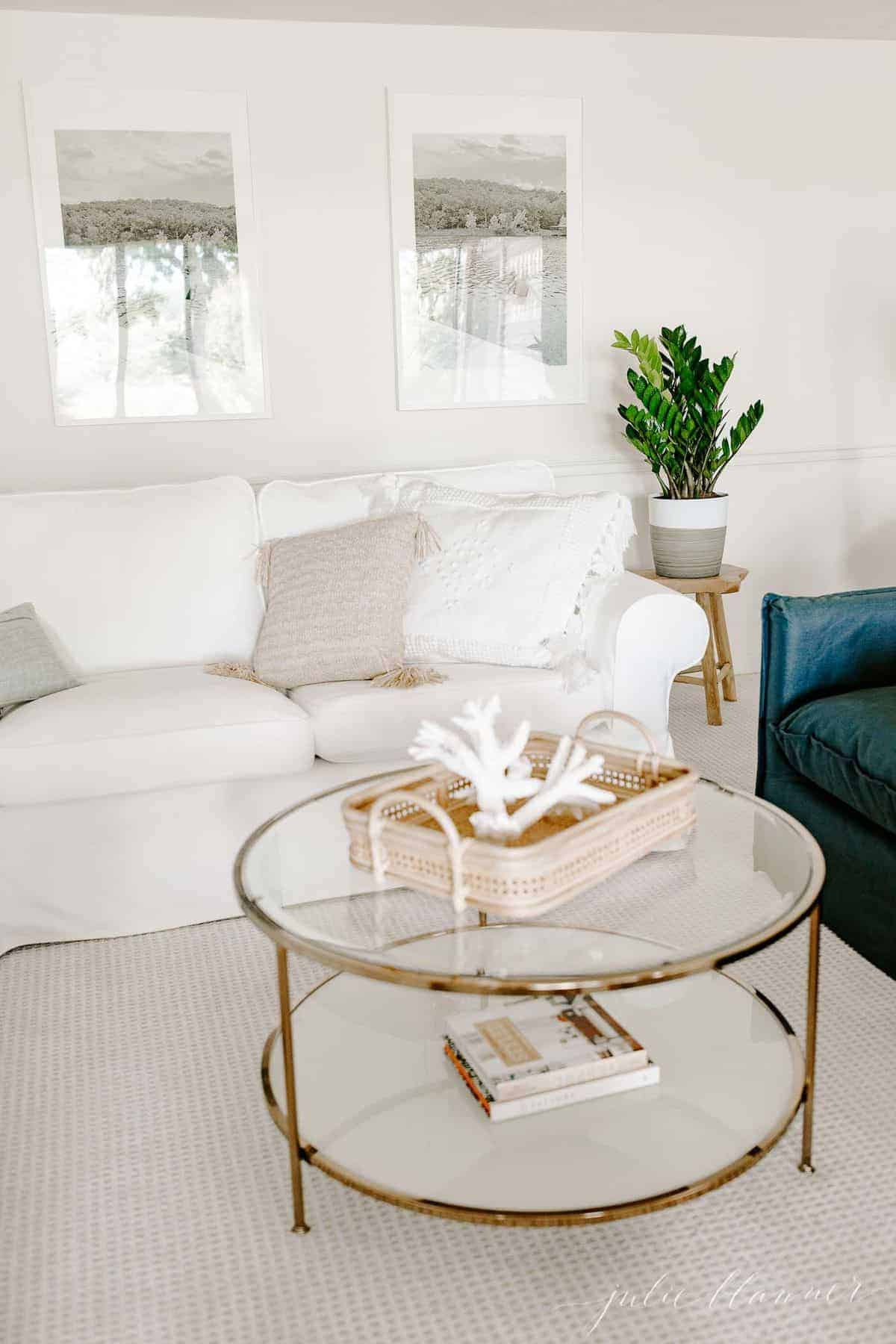 White living room with a white sectional sofa, pillows, and a glass and brass coffee table.