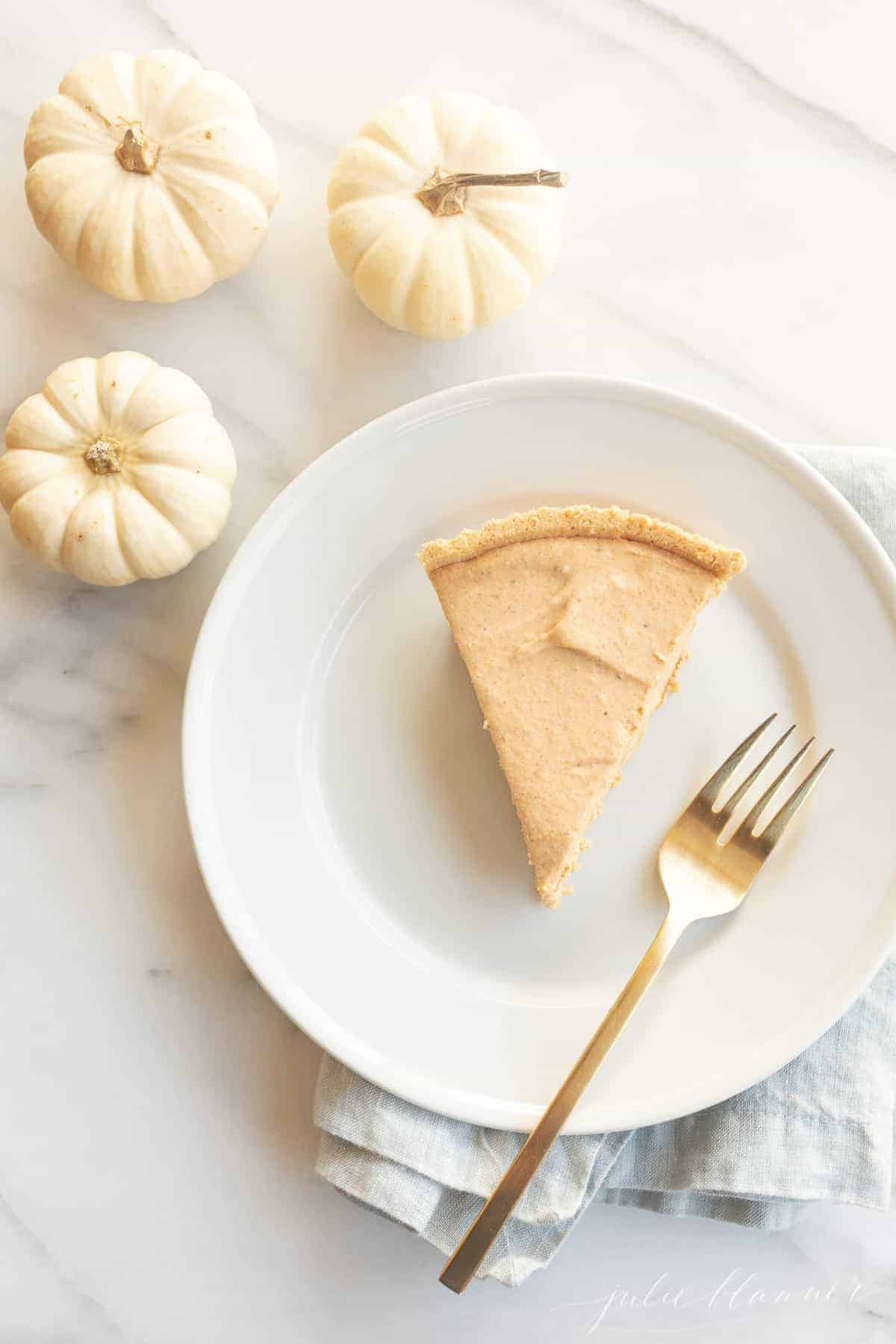 pumpkin cheesecake on a plate with napkin fork and mini pumpkins by plate