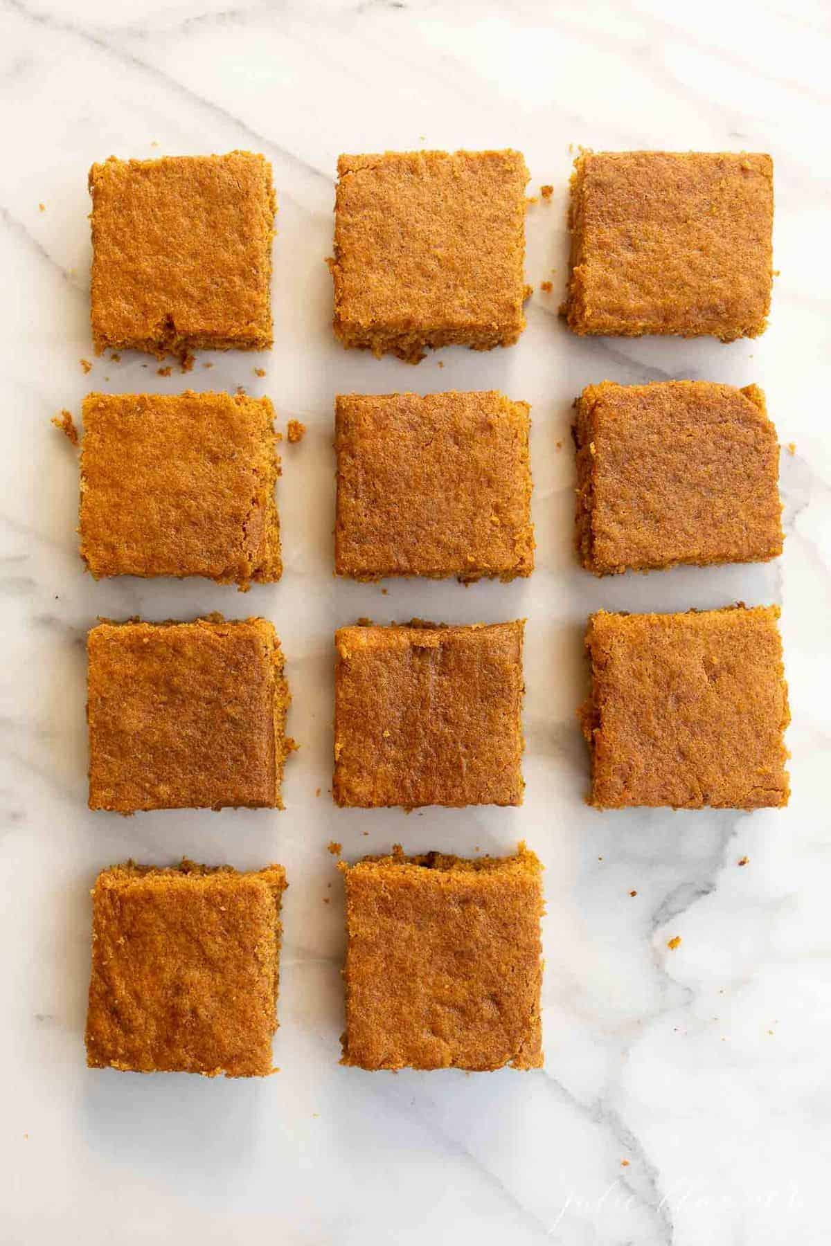 Marble surface with cut pumpkin bars placed neatly together.