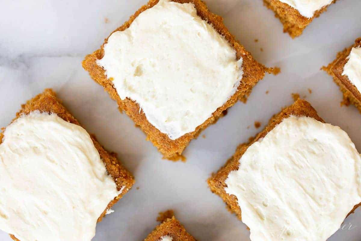 White marble surface with a close up of pumpkin bars cut and covered in cream cheese frosting.