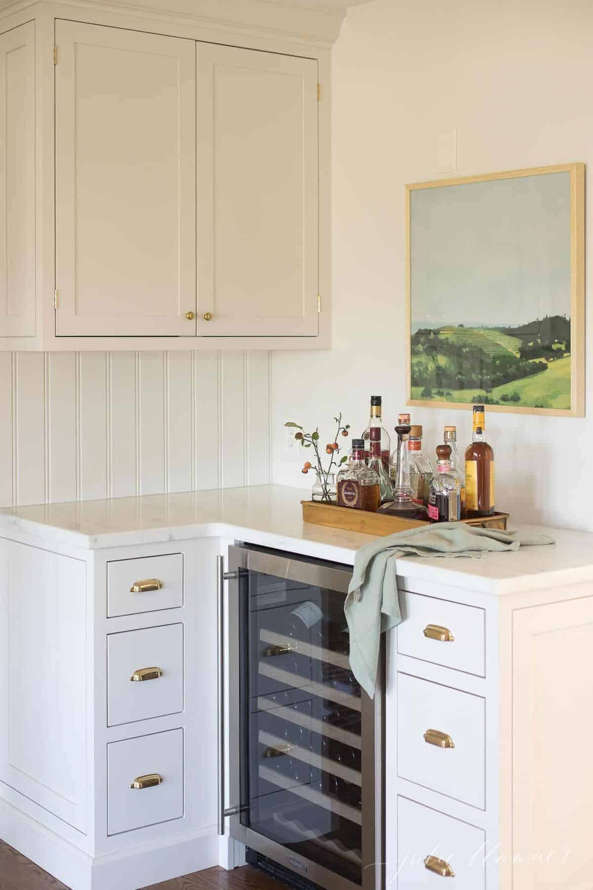 White kitchen cabinets with a bar area and wine fridge, fall berries to the side.
