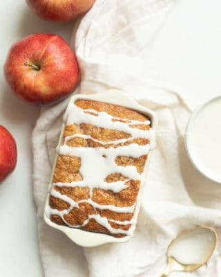 A white surface, apples and frosting to the side, with a loaf of apple bread, glaze drizzled on top.