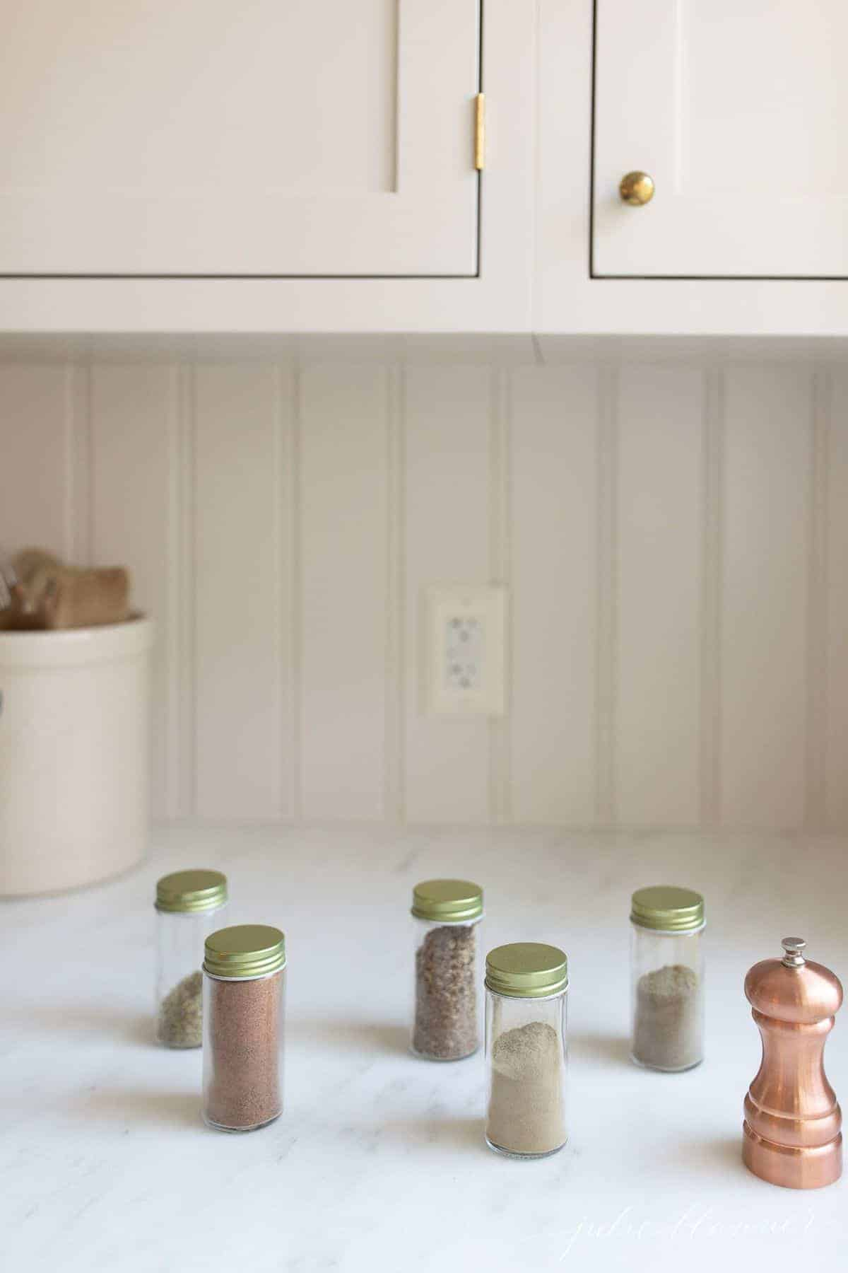 White kitchen with jars of spices in a row for poultry seasoning mix.