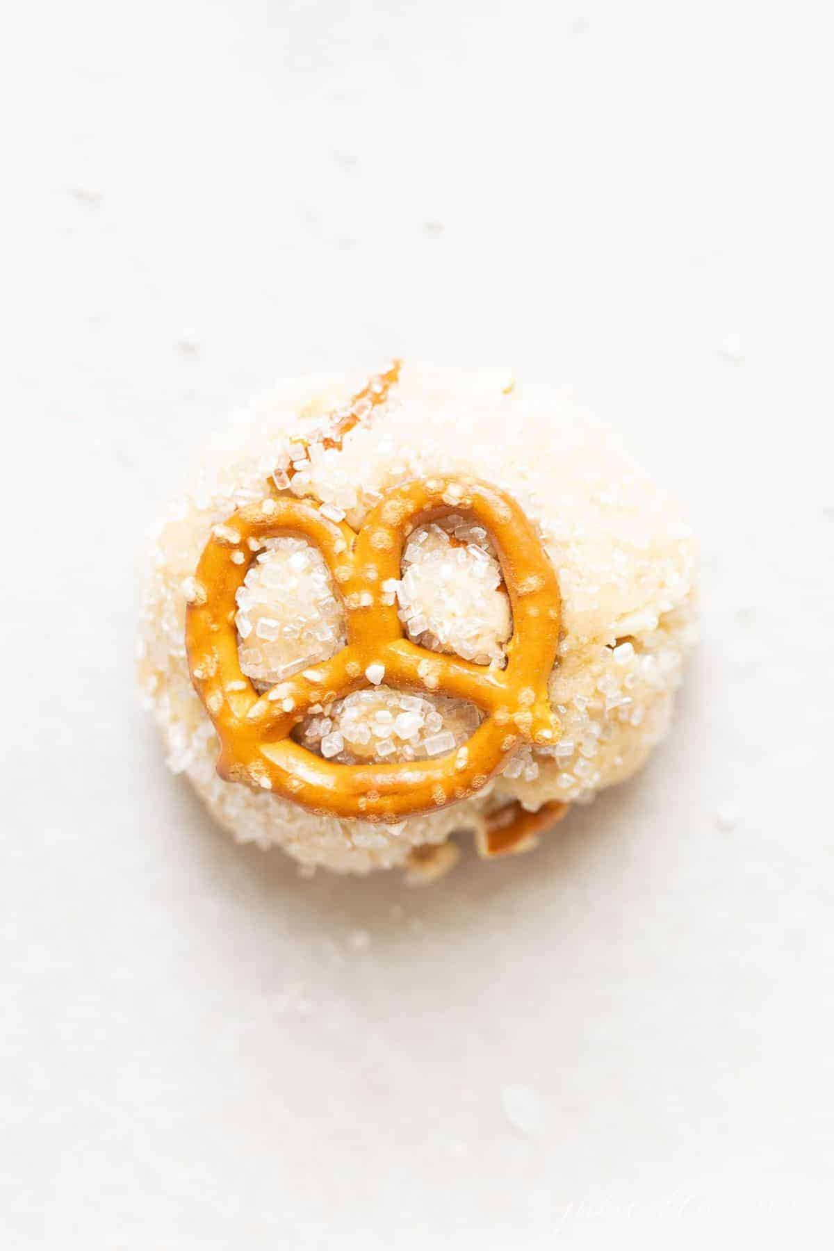 White surface with a cookie dough ball topped with pretzel.