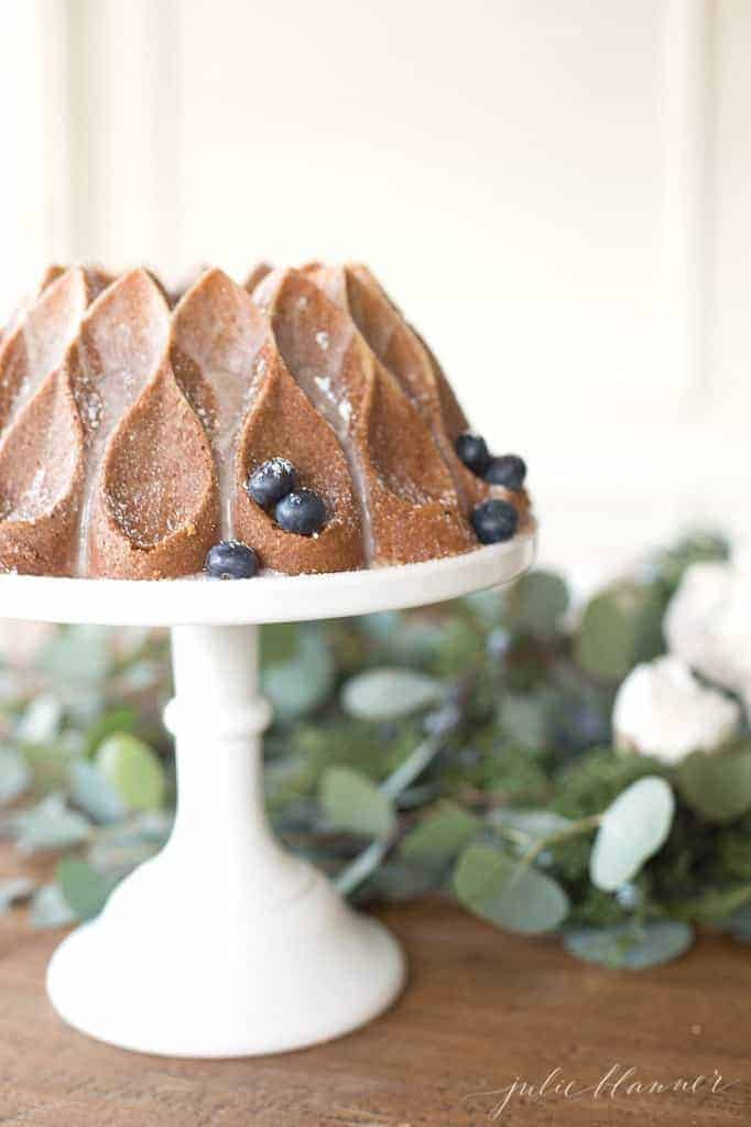 A dining table with flowers, and a bundt cake with blueberries on a tray to the side.