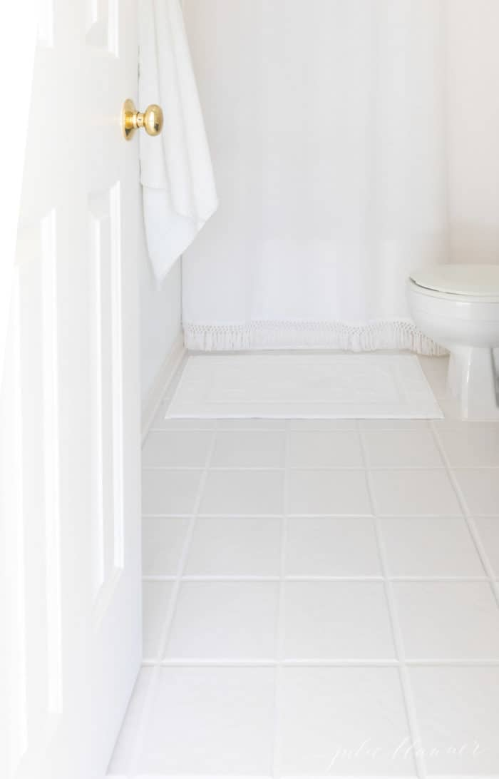 WHITE BATHROOM WITH WHITE TILE AND TILE GROUT