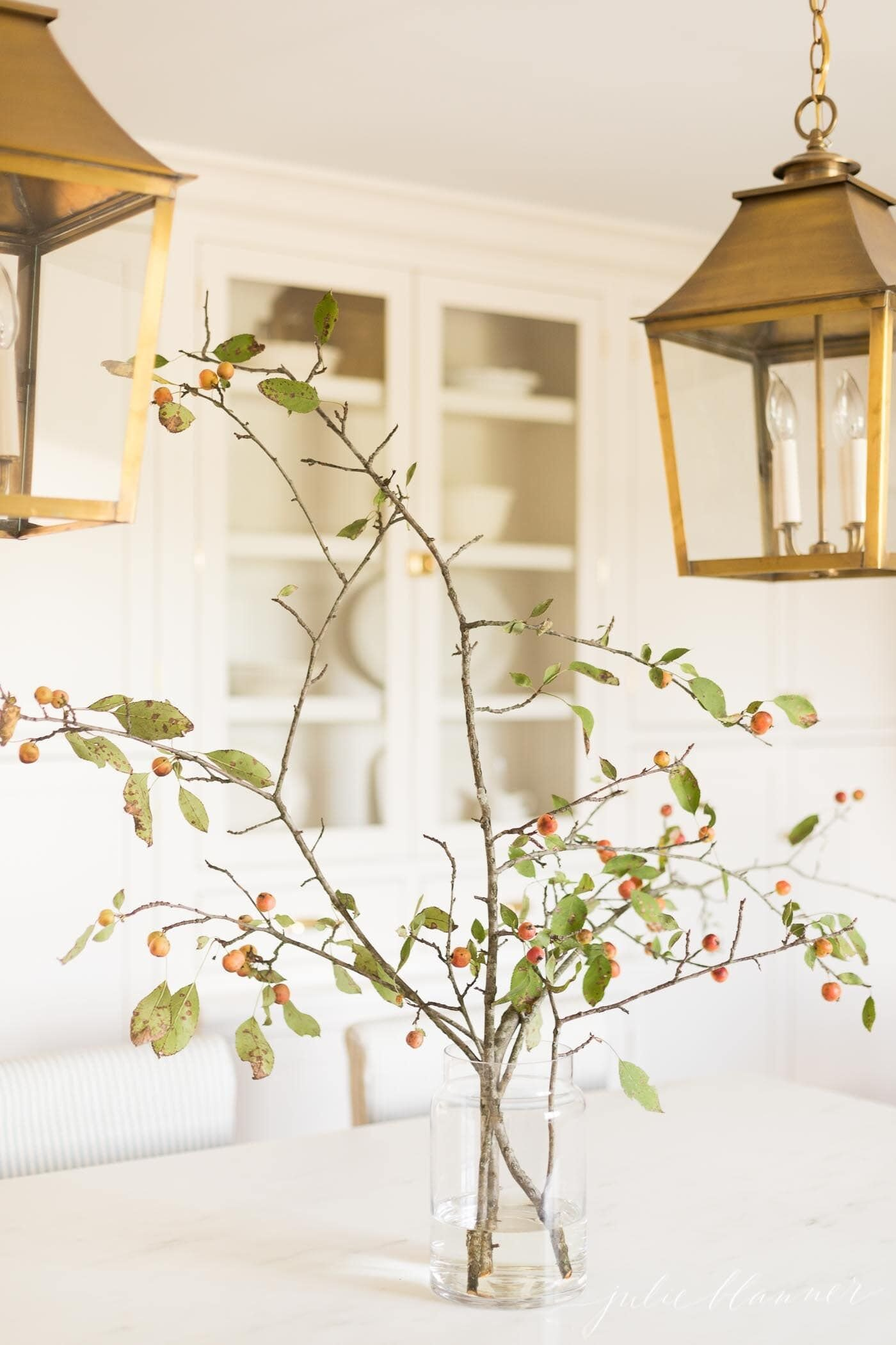 Fall branches with berries in a glass vase, in an all white kitchen, brass lanterns above.