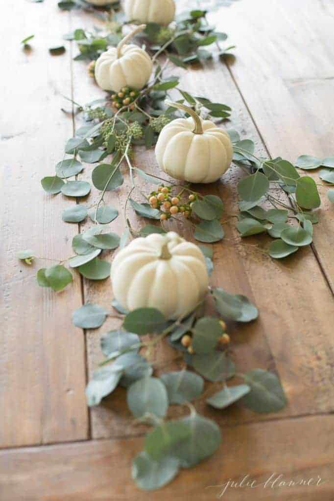 Rustic wooden table with white pumpkins and seeded eucalyptus down the center.