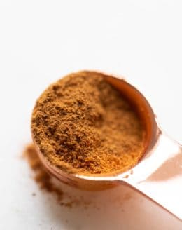 White surface, copper tablespoon filled with pumpkin pie spice mix, loose spices on surface.